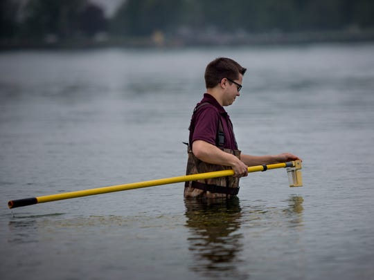 St. Clair County Health Department Environmental Health Aid Adam Czubachowski, 19, of Port Huron, takes a water sample to test for E. coli Thursday, May 25, 2017 at Chrysler Beach in Marysville.