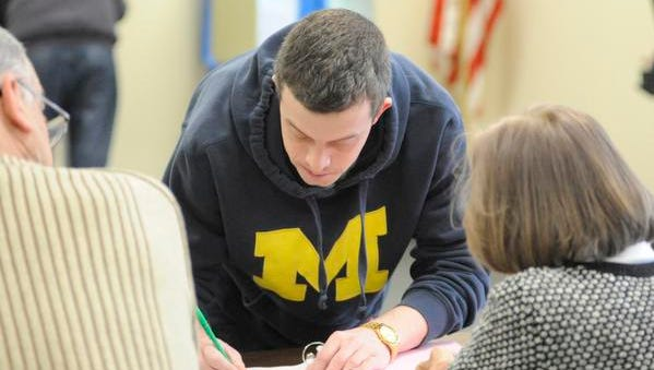 Manitowoc resident Benjamen Weber signs in to vote Tuesday in the spring election at the city's District 9 polling station.