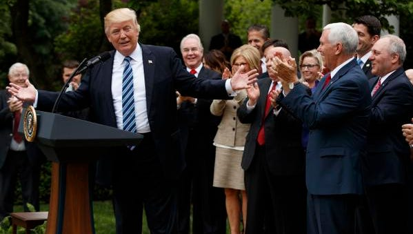 President Donald Trump, accompanied by GOP House members, speaks in the Rose Garden of the White House in Washington, Thursday after the House pushed through a health care bill.