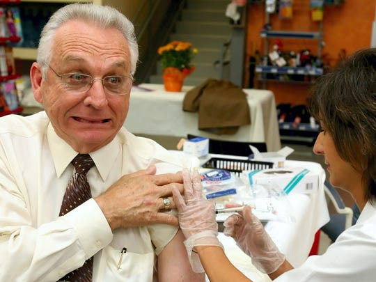 Then-Mayor Henry Garrett grimaces comically while getting a flu shot from Nelda Garcia in October 2007, at H-E-B Plus!.