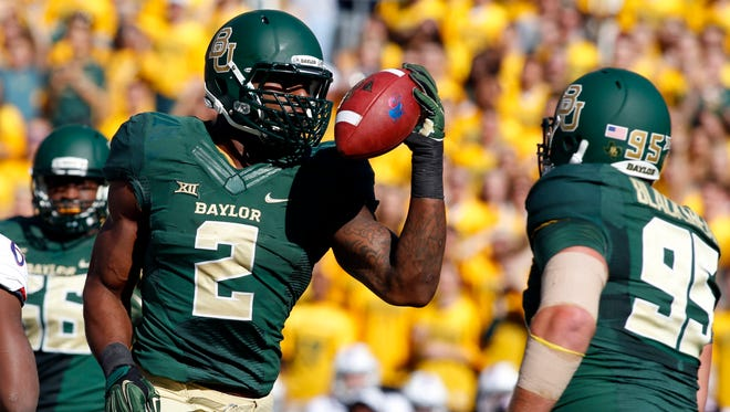 Shawn Oakman celebrates recovering a fumble against Kansas Jayhawks during a game in 2014.