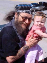 Michael L. Funk, shown here holding one of his  granddaughters,