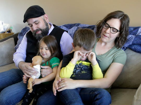 Jake Martinez, 32, holds his daughter Jenny, 3, while his wife Kat, 31, holds their son Joe, 5, at their home Thursday, May 4, 2017, in Murray, Utah. Jake Martinez, who has epilepsy, is worried about health insurance as Republicans move closer to dismantling the Obama health care system, known as the Affordable Care Act, which he and his wife use. (AP Photo/Rick Bowmer)
