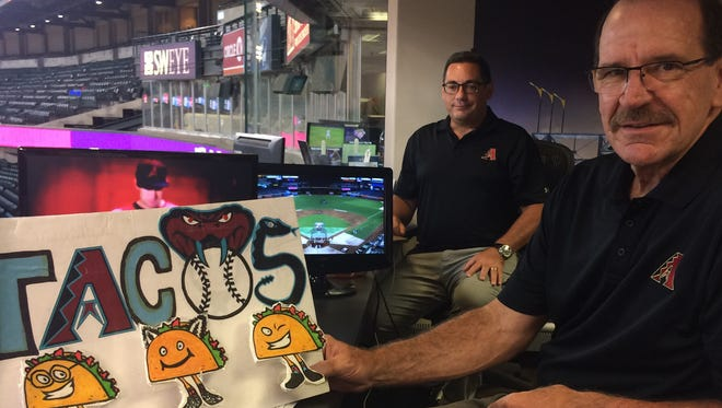 Arizona Diamondbacks broadcasters Steve Berthiaume and Bob Brenly pose in the broadcasting booth at Chase Field with the fan-made sign they hold up whenever the team scores five runs, triggering a free taco promotion.
