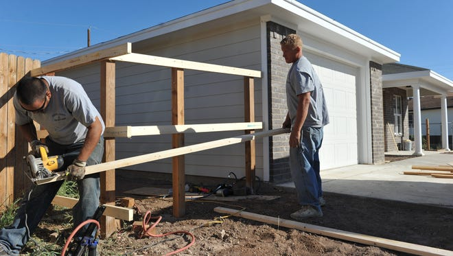 Jason Contreras and Damien Cotton build a fence around a home constructed as part of the through Galilee Community Development Corp. program.