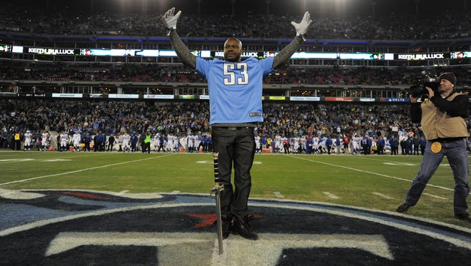 """Former Titans linebacker Keith Bulluck plants the sword into the ground as the """"12th Titan"""" before a game against the Colts on Thursday, Nov. 14, 2013."""