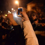 One person takes cell phone video of the celebration in the Cedar Village area late Friday after the Spartans defeated Oklahoma in the Sweet 16.