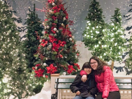 Jorge Jimenez and his sister Ana pose for photos in front of a holiday display at Country Christmas at the Country Springs Hotel in Pewaukee in 2015.