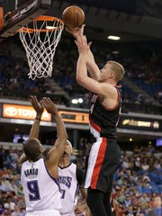 Portland Trail Blazers center Mason Plumlee, right, shoots over Sacramento Kings' Rajon Rondo, left, and Willie Cauley-Stein, center, during the first quarter of an NBA basketball game Tuesday, April 5, 2016, in Sacramento, Calif.
