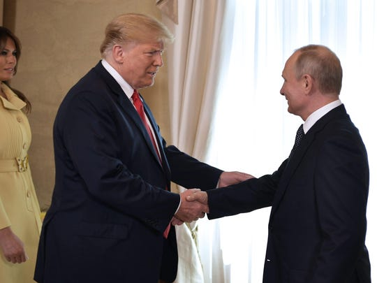 President Donald Trump shakes hands with Russia's President Vladimir Putin ahead of a meeting in Helsinki, on July 16, 2018.