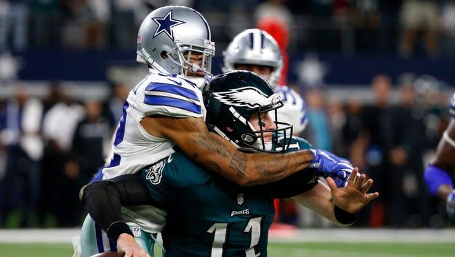 Philadelphia Eagles quarterback Carson Wentz (11) is sacked by Dallas Cowboys cornerback Orlando Scandrick, left, in the second half of Sunday's game in Arlington.