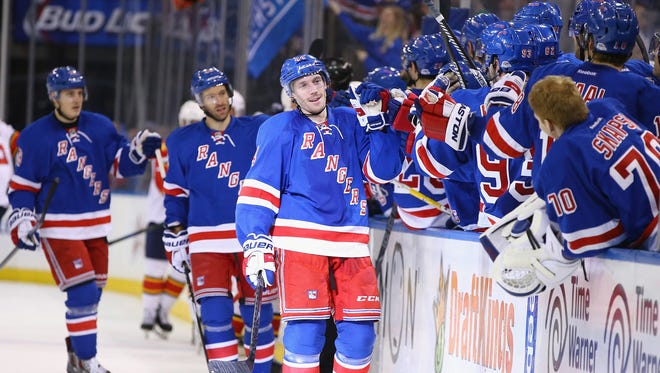 Matt Hunwick gets high-fives from his Rangers teammates after his third-period goal Sunday. Hunwick's goal, his first with the team, wound up being the winner.