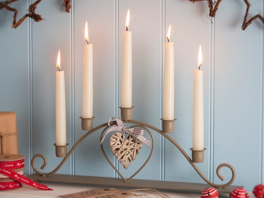"This shaker-style five-candle candelabra has a wicker heart detail and a rustic ""country cottage"" feel."