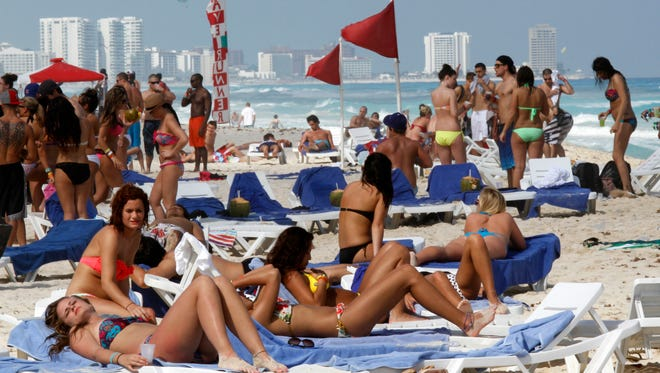Spring breakers gather on the beach in Cancun, Mexico. Flexibility in choosing a destination, among other strategies, can help you save money during this popular travel time.
