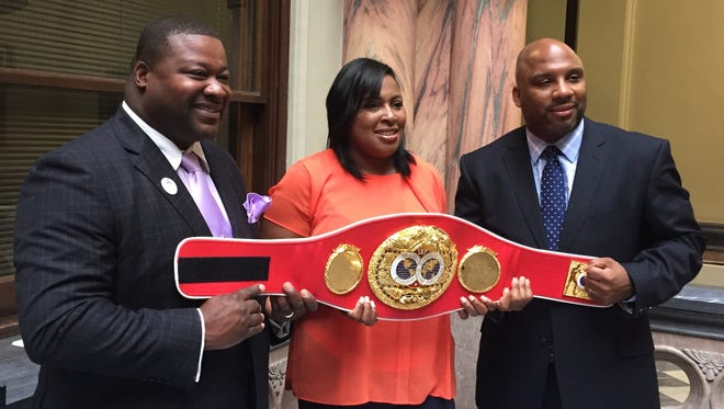 """From left, Monroe County Legislator Willie Lightfoot, Mayor Lovely Warren and the Rev. Rodney Roberts hold the replacement world boxing championship belt that will be given 1993 IBF  champ Charles """"The Natural'' Murray on Saturday, Sept. 13 at Frontier Field."""