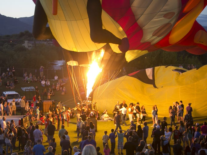 People gather around a balloon while the envelope is