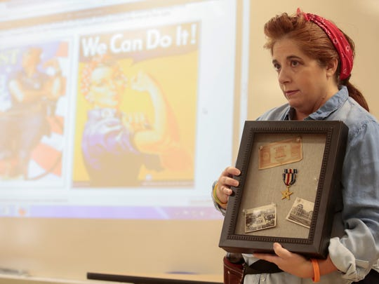 Teacher Vickie Hebert holds a World War II soldier's memorabilia during a 1940s symposium at South Louisiana Community College's Early College Academy in Lafayette Nov. 15, 2016.