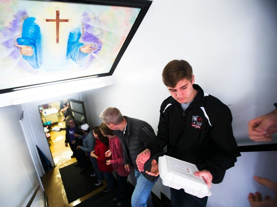 "November 23, 2016 - Max Pleban, 16, passes along a Thanksgiving meal during a Feed the 400 community event at the Calvary Rescue Mission on Wednesday. A group of about 75 people formed a ""human conveyor belt"" to pass the meals to a waiting truck to be deliver to those in need. Each Thanksgiving Eve staff, volunteers and guests (homeless men) at Calvary Rescue Mission serve their neighbors in the Gaston Park community by delivering turkey dinners with all the trimmings to families in the community."