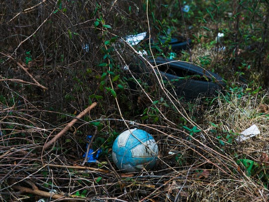 A discarded basketball, a used tire and other debris