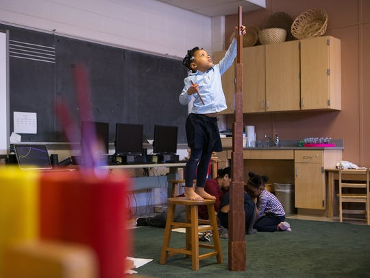 Preschooler Chayce Patton, 4, uses a chair as she does a broad stairwell project where she stacks the blocks together at Montessori Academy at Christina.