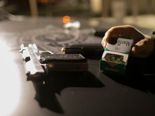 A pistol and illegal pills seized from a suspect by