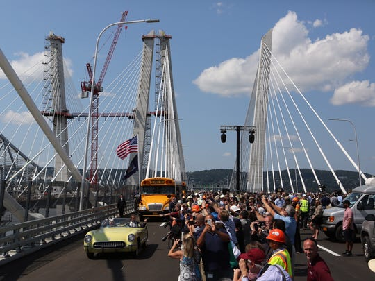 "Onlookers celebrate and take photographs as Gov. Andrew Cuomo, driving a yellow 1955 Corvette with Pearl Harbor survivor Armando ""Chick"" Galella, leads a procession across the new Tappan Zee Bridge on Thursday during opening ceremonies."