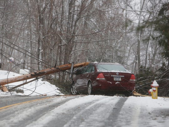 A power line and pole lays on a car at Locust Avenue