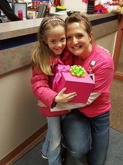 Natasha Fuller, 8, gets a hug from Oakfield Elementary School teacher Jodi Schmidt, who donated her kidney to the little girl.