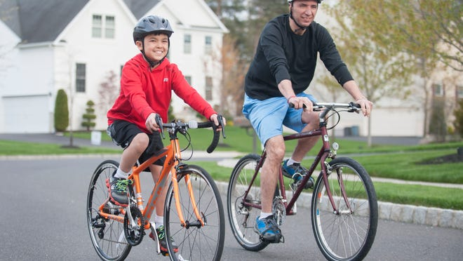 Alec Kazandjian, 11, rides his bike with his father, Hakop Kazandjian, near their Mount Laurel home.