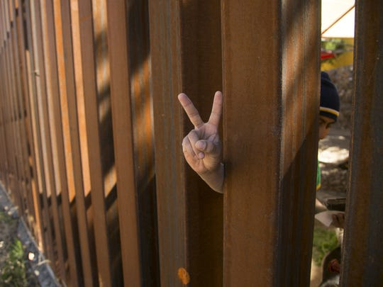 Freddy Perez, 26, flashes a peace sign through the border fence in Nogales, Arizona.