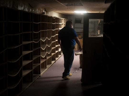 Monroe Township's Public Works Superintendent Mike Calvello walks past warped bookshelves inside of the old Monroe Township public library.