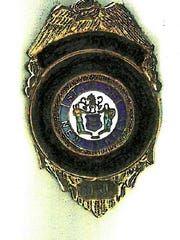 A redacted sketch of the badge of an unidentified commissioner