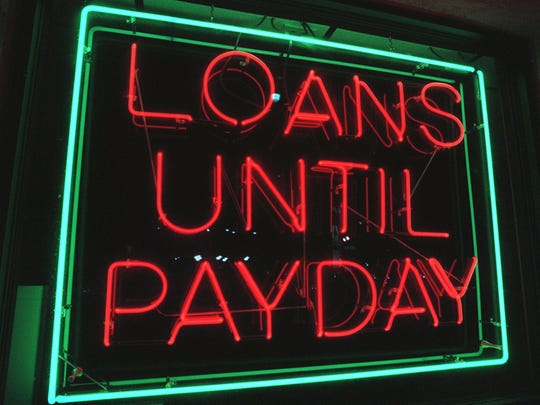 Bright lights and signs attract customers to payday/tile loan businesses.