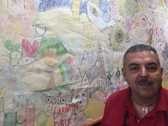 Juan Vasquez shows off his wall of inspiration at 3 in 1 Restaurant.