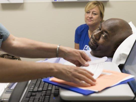Registered nurse Joan Zittnan talks with Derek Mosley