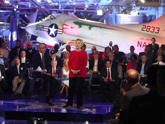 Matt Lauer looks on as Hillary Clinton speaks during