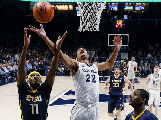 Xavier's Kaiser Gates (22) and East Tennessee State's Devontavius Payne (11) battle for a rebound in the first half of an NCAA college basketball game, Saturday, Dec. 16, 2017, in Cincinnati. (AP Photo/John Minchillo)