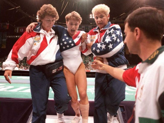 Larry Nassar, front right, reaches to assist U.S. gymnast Kerri Strug, center, who screams in pain as she is carried from the floor by team officials after she injured her ankle during the 1996 Olympics in Atlanta.
