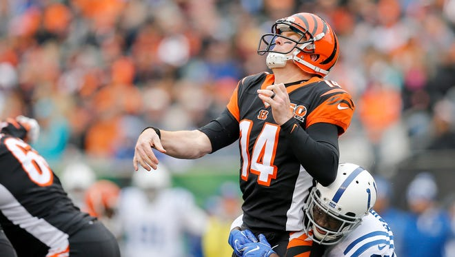 Cincinnati Bengals quarterback Andy Dalton (14) is hit hard from the back by Indianapolis Colts cornerback Nate Hairston (27) after throwing in the second quarter of the NFL Week 8 game between the Cincinnati Bengals and the Indianapolis Colts at Paul Brown Stadium in downtown Cincinnati on Sunday, Oct. 29, 2017.