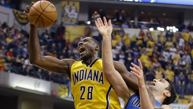 Indiana Pacers' Ian Mahinmi (28) grabs a rebound against Dallas Mavericks' Zaza Pachulia (27) during the first half of an NBA basketball game Wednesday, Dec. 16, 2015, in Indianapolis. (AP Photo/Darron Cummings)