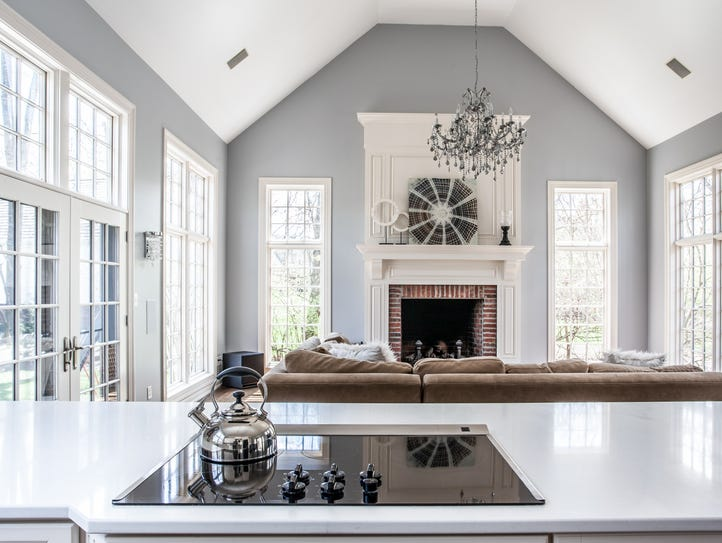 The great room has high ceilings and a large fireplace.