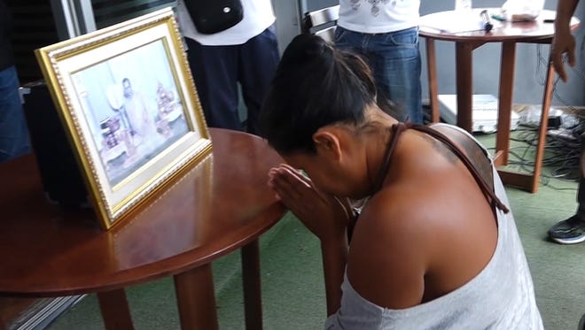 In this image made from video taken on Sunday, Oct. 16, 2016, Umaporn Sarasat, 43, pays respects in front of a portrait of Thailand's King Bhumibol Adulyadej in Koh Samui, Thailand. She is accused of insulting the country's late king and was forced to kneel before his portrait outside a police station on the tourist island of Samui as several hundred people bayed for an apology.