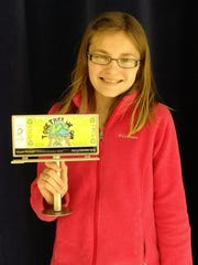 Grace Draeger of Woodmore Elementary holds her winning Earth Day billbooard design.