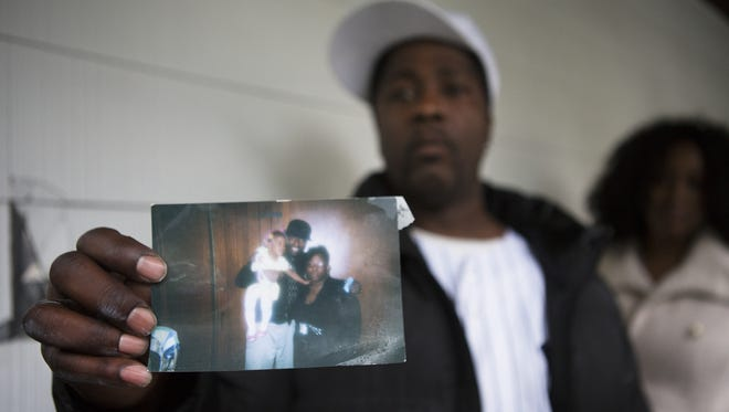 Michael Davis Sr. holds up a photograph of his brother, Richard Gregory Davis posing with his daughter, Destanee Davis-Parson and granddaughter, N'zriyah Davis, at his home on Sunday, May 31, 2015. Richard Gregory Davis died earlier today after being tased by police.