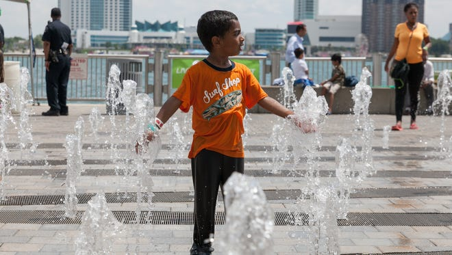A young boy plays in the fountain in front of the Renaissance Center in downtown Detroit on June 23. Warmer weather is in the forecast for this weekend.