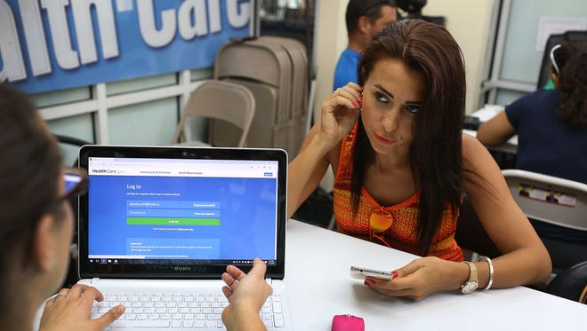 Alina Nurieva, right, sits with Gabriela Cisneros, an insurance agent from Sunshine Life and Health Advisors, as she picks an insurance plan available in the third year of the Affordable Care Act at a store setup in the Mall of the Americas on Nov. 2, 2015, which was the second day of enrollment. Others often start far later and even past the deadline.