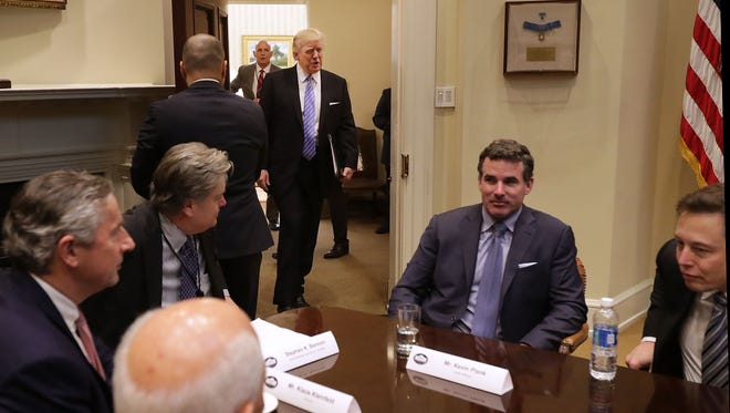 U.S. President Donald Trump (C) walks into the Roosevelt Room for a meeting with Mark Sutton of International Paper, Jeff Fettig of Whirlpool, White House Senior Counselor Steve Bannon, Kevin Plank of Under Armour, Elon Musk of SpaceX (L) and other other business leaders at the White House January 23, 2017 in Washington, DC.