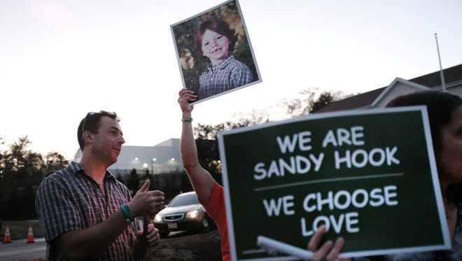 Mark Barden holds up a picture of his son Daniel who was killed in the Sandy Hook masracre during a vigil remembering the 58 people killed in Sunday's shooting in Las Vegas and calling for action against guns on October 4, 2017 in Newtown, Connecticut. The vigil, organized by the  Newtown Action Alliance, was held outside the National Shooting Sport Foundation and looked to draw attention to gun violence in America. Twenty school children were killed at the Sandy Hook Elementary School shooting on December 14, 2012.