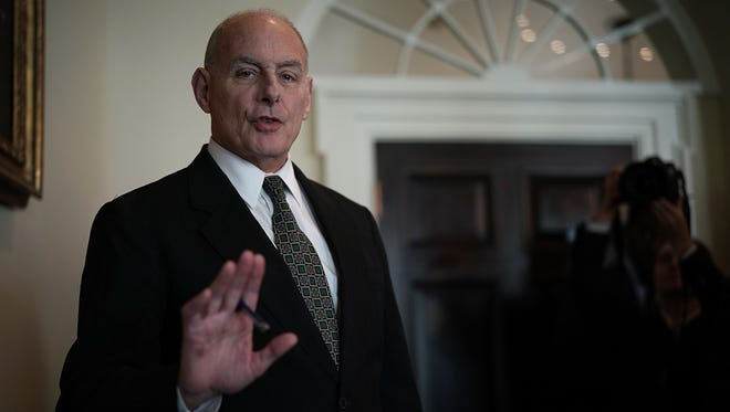 White House Chief of Staff John Kelly signals photographers to stop taking pictures of him as President Trump met with members of Congress in the Cabinet Room of the White House Tuesday.
