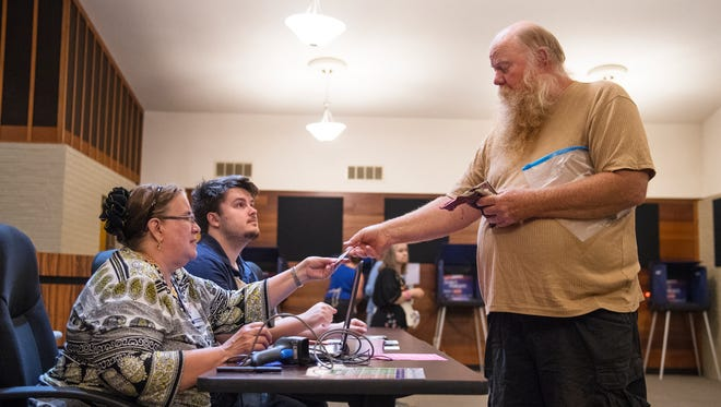 Danny Graham hands his identification to poll worker Kris Cox before voting in the primary elections at Travelers Rest City Hall on Tuesday, June 12, 2018.